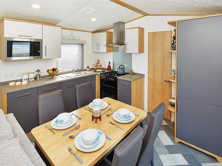 The kitchen is spacious with a centrally positioned dining table and chairs